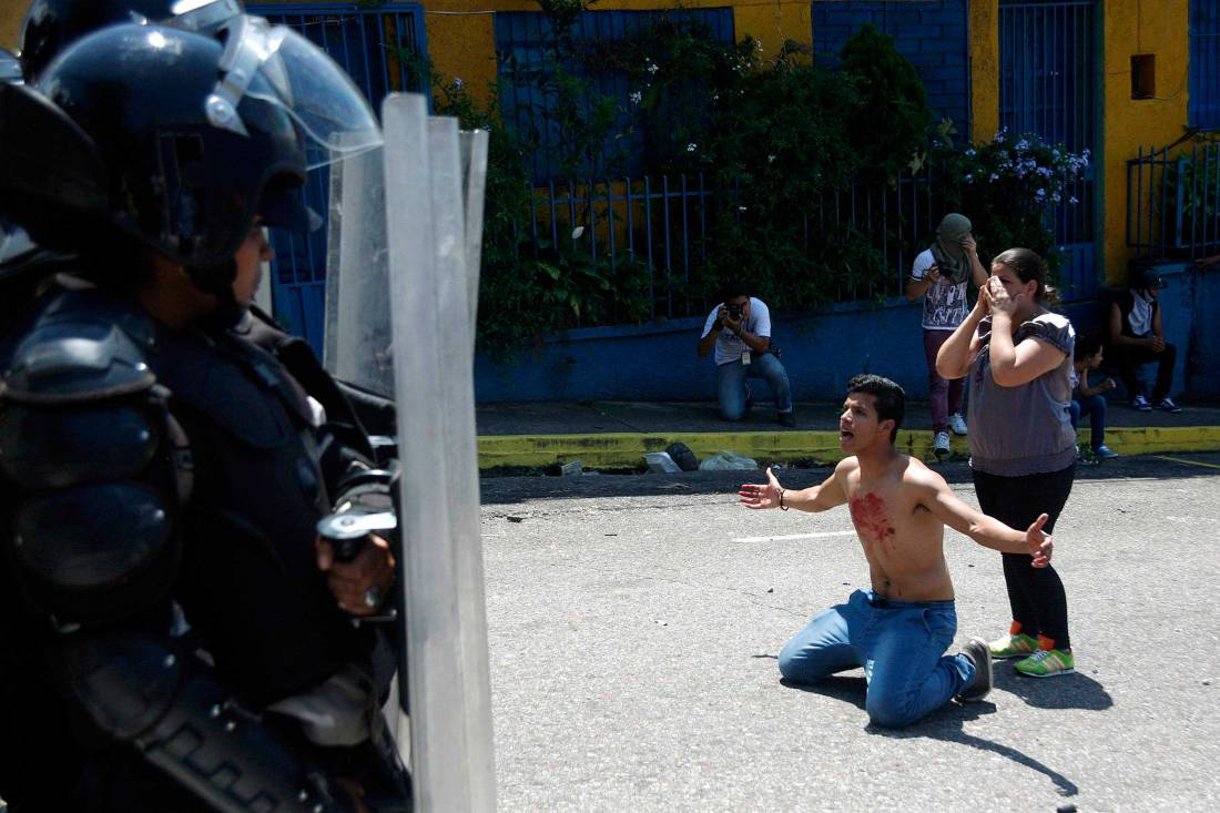 Boy with blood on his chest kneels in front of police after 14-year-old student Kluiver Roa died during a protest in San Cristobal